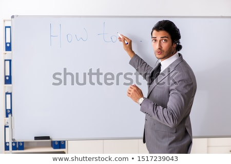 Young handsome businessman in front of whiteboard  Stock photo © Elnur