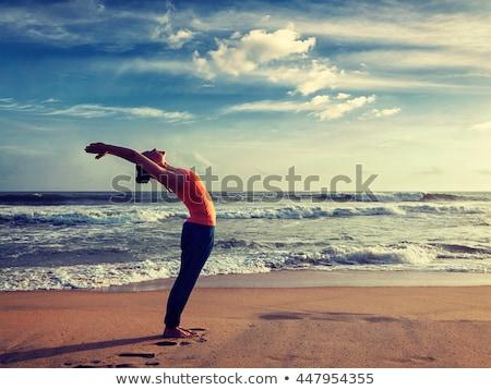 Woman doing yoga Surya Namaskar oudoors at tropical beach Stock photo © dmitry_rukhlenko