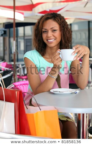 20 years old metis woman is drinking coffee on a terrace, she did shopping before Stock photo © photography33
