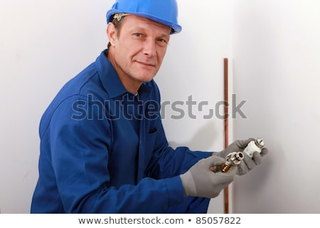 Stock photo: plumber showing plumbing pieces