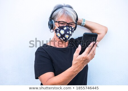 Attractive woman using her headphones while standing against a white background stock photo © wavebreak_media