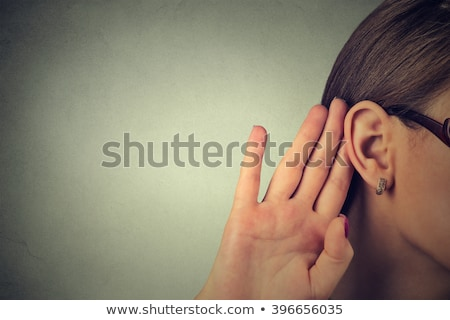 Young female holding hand to ear to listen stock photo © serendipitymemories