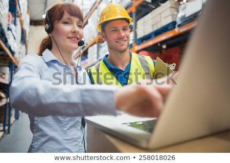 worker in warehouse wearing headset and using laptop stock photo © monkey_business