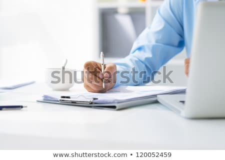 businessman - writing on clipboard Stock photo © dgilder