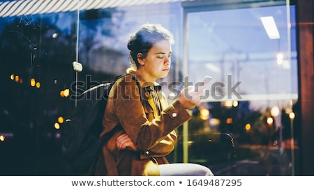young woman sitting waiting on a bench stock photo © dash