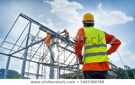 construction workers discussing blueprints stock photo © kzenon