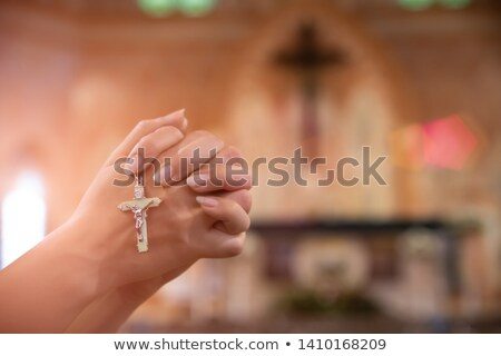Silhouette of man holding rosary and praying  Stock photo © deandrobot