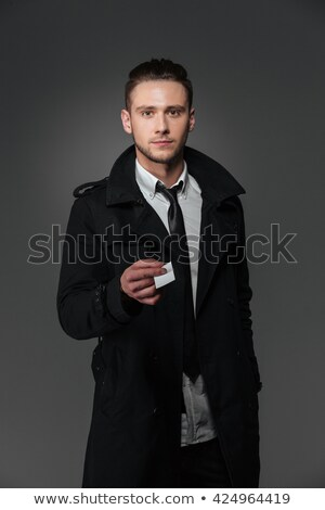 Confident businessman in black coat giving you blank business card Stock photo © deandrobot