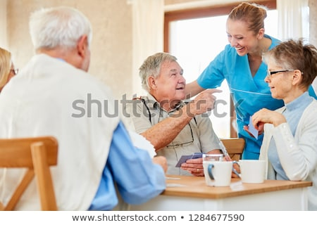 Group of seniors and nurse playing cards in rest home Stock photo © Kzenon