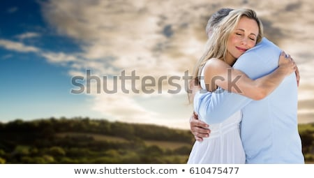 Beautiful couple hugging over cloudy sunset Stock photo © konradbak