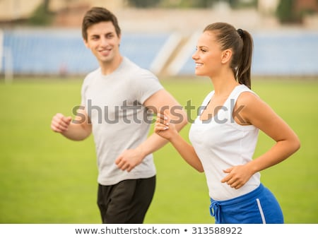 Woman athlete working out with personal trainer on stadium Stock photo © deandrobot