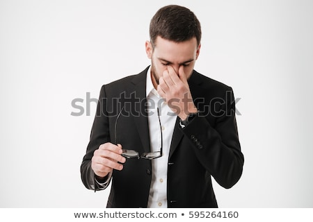 tired bearded young man touching face with hands stock photo © deandrobot