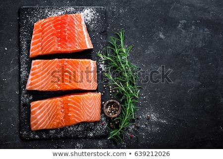 Raw salmon filet on dark slate background, wild atlantic fish Stock photo © yelenayemchuk