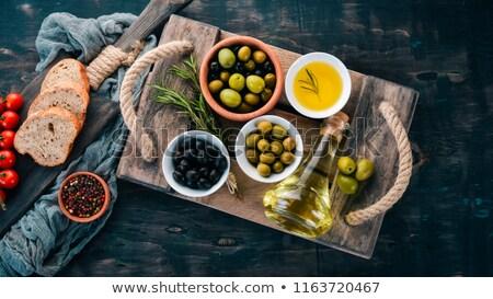 fresh homemade ciabatta bread sliced on stone slate board olive oil and rosemary on wooden backgrou stock photo © yelenayemchuk