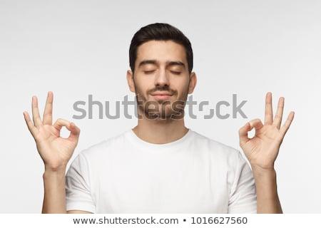 close up of man meditating at yoga studio Stock photo © dolgachov