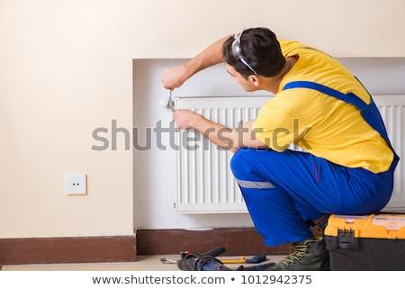 the young repairman contractor repairing heating panel stock photo © elnur