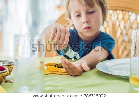 boy using wash hand sanitizer gel in the cafe stock photo © galitskaya
