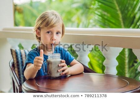 A boy drinks a drink from a carob Stock photo © galitskaya