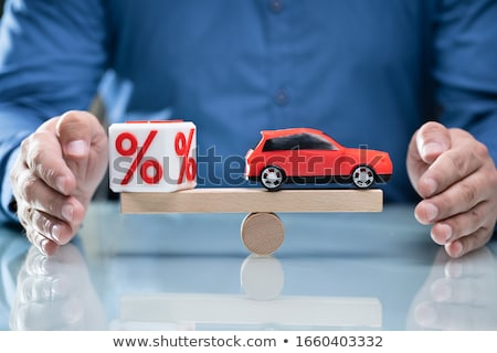 Stock photo: Businessperson Protecting Balance Between Percent Symbol And Car