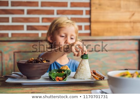 boy eats in a cafe lifestyle a dish consisting of rice fried fish with wood mushrooms and differe stock photo © galitskaya