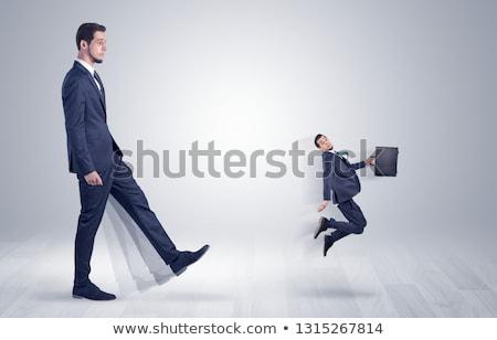 Nagy férfi rúg kicsi ki öltöny Stock fotó © ra2studio