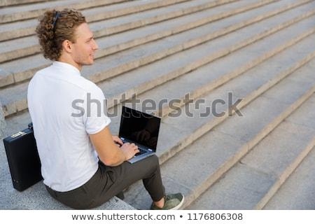 Mosolyog fürtös üzletember aktatáska laptop számítógép beszél Stock fotó © deandrobot