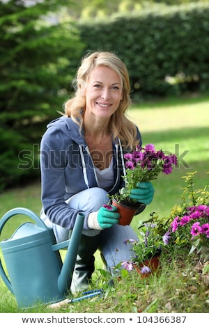 pretty middle aged woman watering plants and flowers stock photo © lightpoet