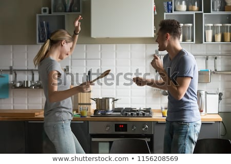 lovely cheerful couple cooking dinner together and having fun at stock photo © boggy