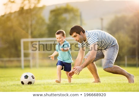Young father with his little son playing football on football pitch Stock photo © Lopolo