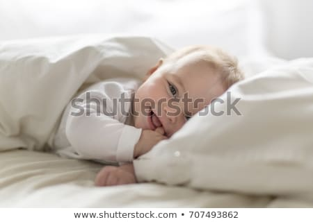 Cute happy 7 month baby girl in diaper lying and playing Stock photo © Lopolo