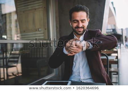 smiling young man checking time on wristwatch Stock photo © dolgachov