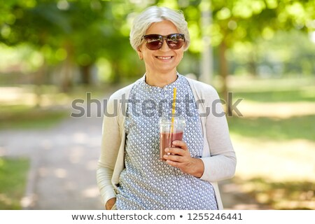 senior woman drinking takeaway shake at park Stock photo © dolgachov
