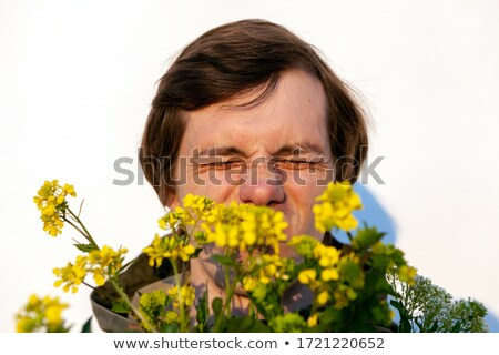 Stock photo: Man blowing his nose in canola field