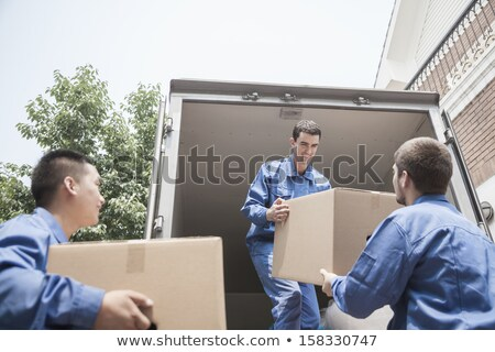 Movers Unloading A Moving Van And Passing A Cardboard Box Stock photo © AndreyPopov