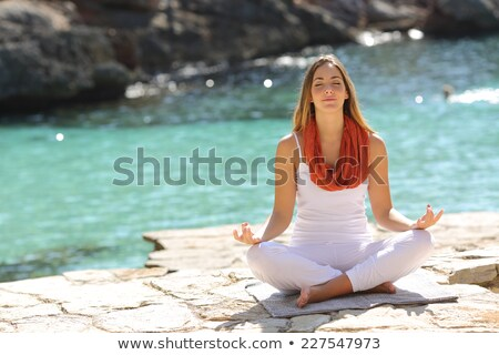Calm lady sitting in lotus position at resort Stock photo © dash