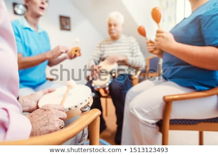 Seniors in nursing home making music with rhythm instruments Stock photo © Kzenon