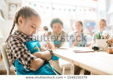 Ragazza braccia seduta desk insegnante Foto d'archivio © pressmaster