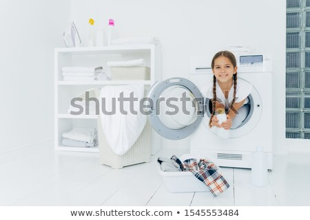 Small girl with appealing appearance, has fun and poses inside of washer, holds detergent, prepares  Stock photo © vkstudio