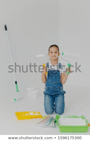 Happy little girl in denim overalls stands on knees, holds paint roller, surrounded with trays with  Stock photo © vkstudio