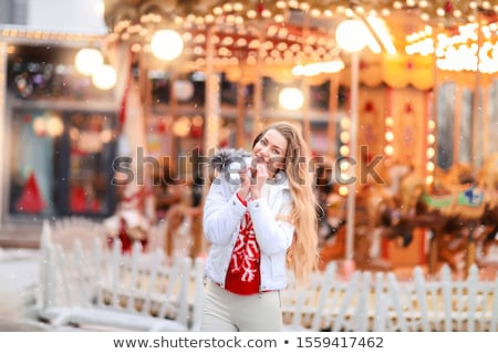 Girl in winter New Year's evening on the background of a festive carousel Stock photo © ElenaBatkova
