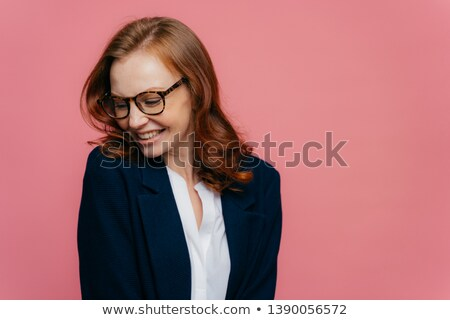 Elegant positive businesswoman focused aside, has sincere smile, wears spectacles, dressed in formal Stock photo © vkstudio