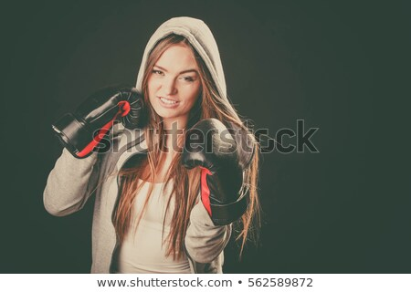 Image of energetic woman wearing sportswear training in boxing gloves Stock photo © deandrobot