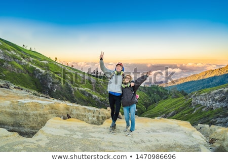 Young tourist man and woman stand at the edge of the crater of the Ijen volcano or Kawah Ijen on the Stock photo © galitskaya