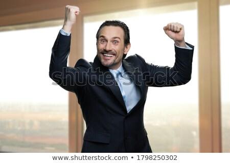 Portrait of happy successful man rejoices his triumph, clenches  Stock photo © vkstudio
