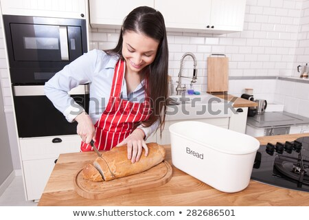 beautiful housewife cutting bread with knife stock photo © vladacanon