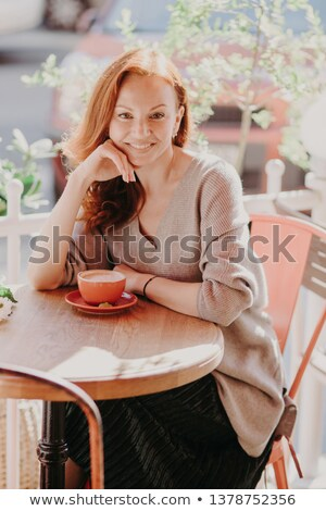 Vertical shot of cheerful foxy female dressed in fashionable clothes, drinks coffee, poses in outdoo Stock photo © vkstudio