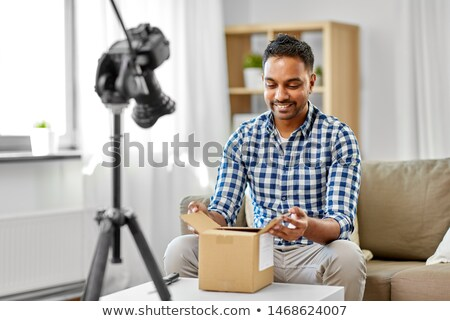 male video blogger opening parcel box at home Stock photo © dolgachov