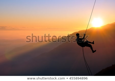 Silhouette of Man Rappelling Stock photo © pancaketom