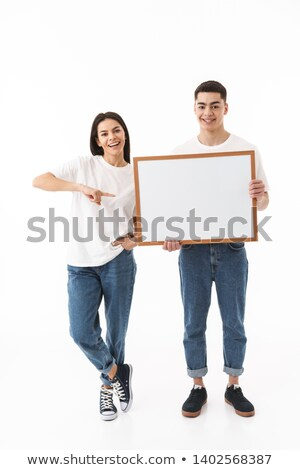 couple of casual people presenting a big blank billboard stock photo © feedough