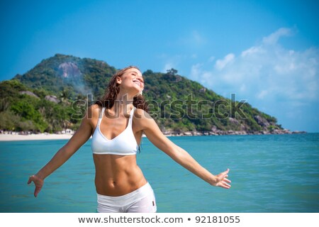 young woman in a bikini splashing in the sea stock photo © smithore